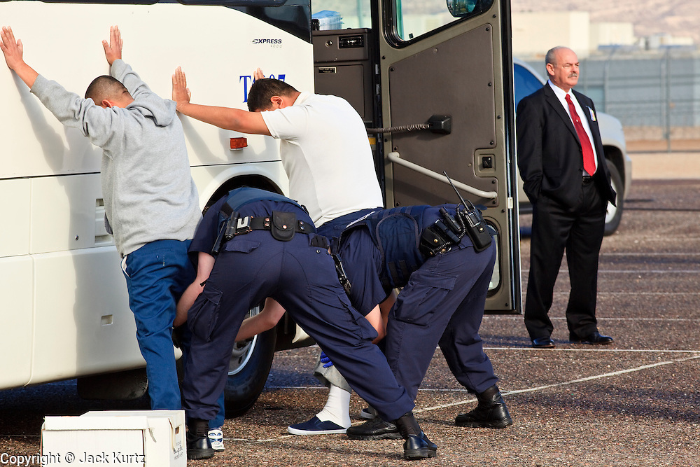 28 JANUARY 2010 -- BUCKEYE, AZ: William White (CQ) RIGHT, warden of Lewis Prison, stands in watches as undocumented immigrant inmates are searched and handcuffed by ICE officers before boarding an ICE bus at Lewis Prison. The Arizona Department of Corrections transferred 51 undocumented immigrant inmates from state control to the Immigration and Customs Enforcement at Lewis Prison in Buckeye Thursday morning. The inmates have less than 90 days left on their sentences and will be deported to their countries of origin when they finish their prison terms.   PHOTO BY JACK KURTZ