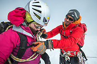 A male mountain guide assists a female climber with safety knot on a cold Winter day on Glacier Blanche.