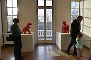 Roslyn, New York, USA. January 2, 2015.  Visitors look at Dinosaur and at Torso (2006), both in red polyresin, by Sui Jianguo (b. 1956) at the Nassau County Museum of Art China Now and Then Exhibit.