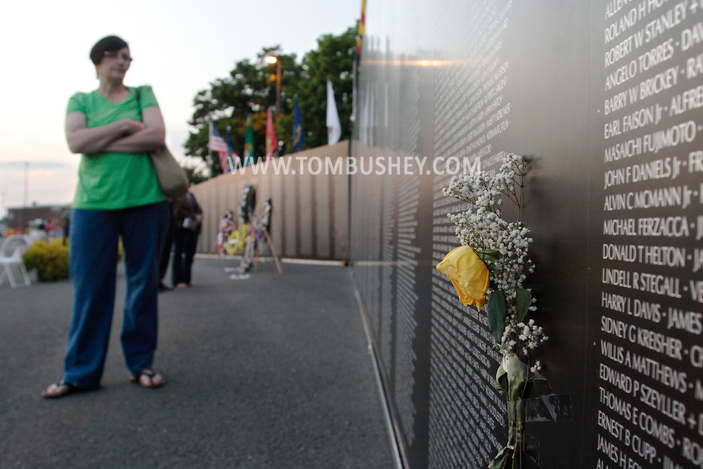 Newburgh, NY - A woman looks at the names on the Vietnam Veterans Memorial Moving wall at Stewart International Airport on June 6, 2009. A yellow rose is taped to the wall at right.