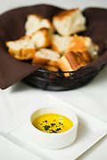 A basket of focaccia bread and oil for dipping.