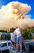 The Lawson family of Bountiful watches smoke fill the sky, July 10, 2003 as a blaze moves northward, north- east of Bountiful Peak in Farmington. The first major fire in Davis County brought thousands of area residents from their homes as they watched firefighting helicopters and planes drop numerous loads of water and fire retardant in an attempt to bring the fire under control.  Colin Braley.                               .