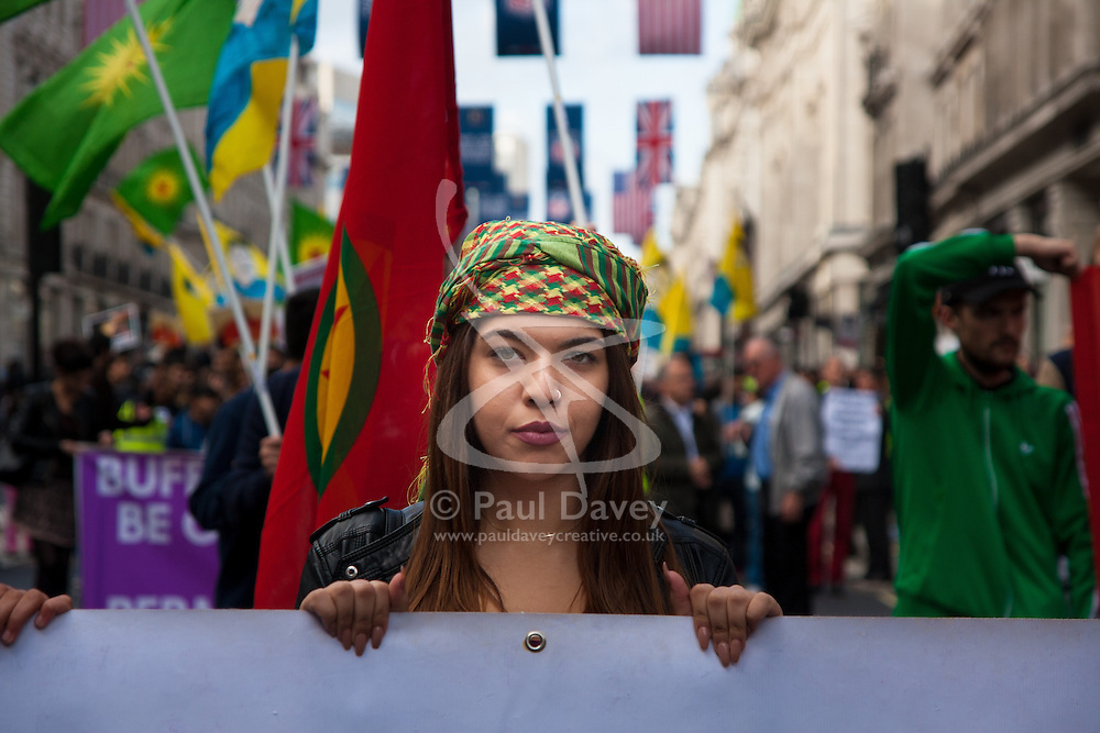 London, October 19th 2014. Hundreds of London's Kurdish community march throgh the capital in protest against ISIS and the Turkish government who they accuse, by not getting involved in military action against ISIS, of using the Jihadists to wipe out Kurds who have long been campaigning for an independent Kurdistan. PICTURED: A young woman holds the camera's gaze as she marches along Regents street.
