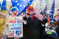 London, UK. 14th February, 2019. Anti-Brexit activists Madeleina Kay, also known as EU Super Girl, and a man dressed as the devil protest outside the Houses of Parliament in Westminster.