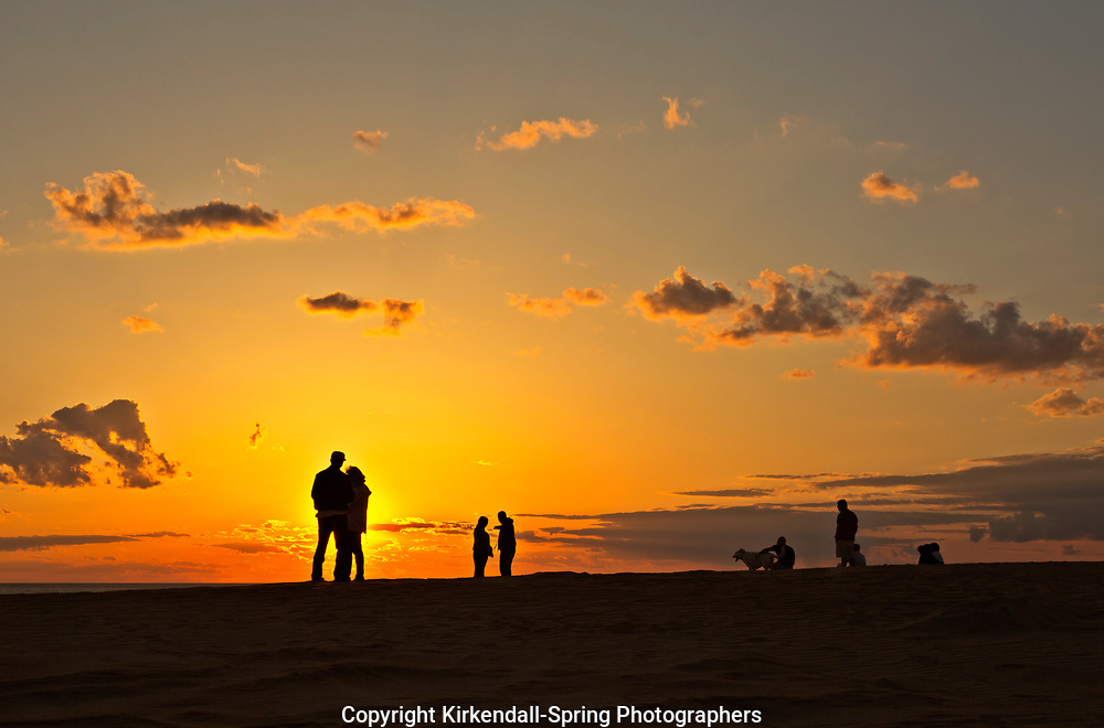 NC01428-00...NORTH CAROLINA - Watching the sunset from a tall sand dune, a popular activity at Jockey's Ridge State Park on the Outer Banks at Nags Head.
