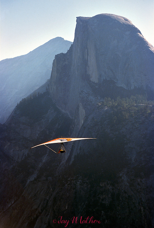 A hang glider soars off Glacier Point with Half Dome in the background.  The sport in the park is allowed and is regulated and monitored by rangers.  July 1989.