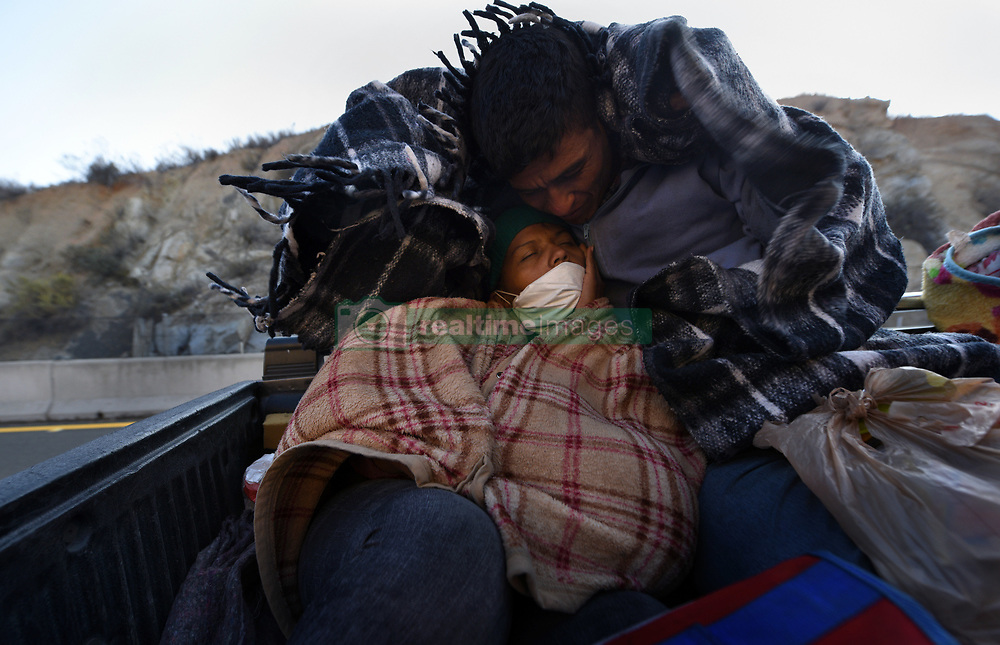 November 20, 2018 - Mexicali, Mexico - A young couple from Honduras with their 1-year-old baby hitch a ride November 20, 2018 with others from migrant caravan that had stopped to rest in Mexicali, Mexico. They endure the cold wind as they drove through La Rumorosa mountain road to a shelter in Tijuana where they will wait in hopes of crossing the border to America.  They started October 12 on their journey with caravan. (Credit Image: © Carol Guzy/ZUMA Wire)