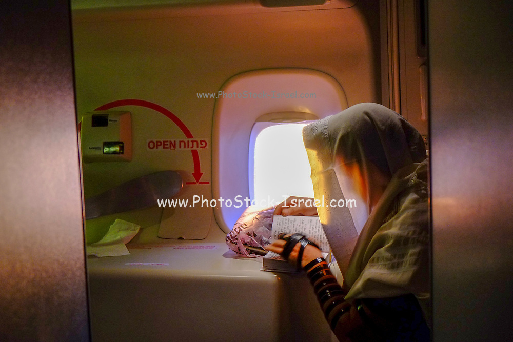 A man is putting on a tefillin and praying at sunrise inside of an airplane over the ocean