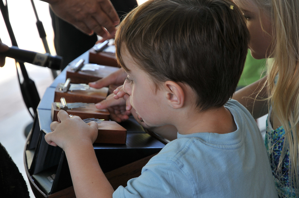 Kids try their hand at the kalimba during the 2011 Tucson Folk Festival Children's Show. Event photography by Martha Retallick.
