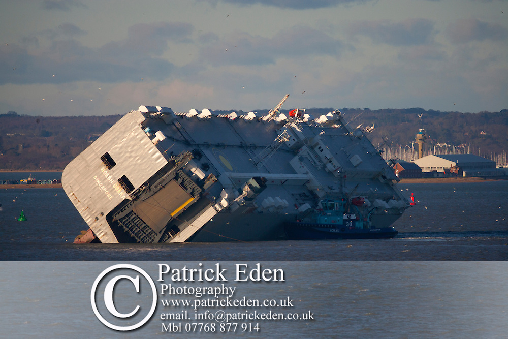 06/01/2015 Cowes Isle of Wight. Life goes on in The Solent. Captsized car carrier Hoegh Osaka in the late afternoon sunshine. Surveyors and survey ships are in attendence to assess the state of the ship and its cargo. Windy weather is expected in the next few days.