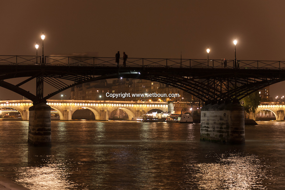 France. Paris. 1st district Art bridge on the Seine river at dusk view from the quai du Louvre in the distance the pont Neuf / le pont des arts sur la Seine