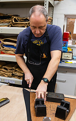 Using a very sharp knife and a wooden pattern, a single cut slices through with segments of an umbrella's cover.Craftspeople at Fox Umbrellas Ltd, a company in Croydon, Surrey, that has been going for over 150 years hand build quality umbrellas. Croydon, Surrey, March 06 2019.