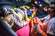 "30 NOVEMBER 2012 - BANGKOK, THAILAND: A man injured in a motorcycle accident is taken to a hospital by volunteer medics with the Ruamkatanyu Foundation during a Friday night shift. The Ruamkatanyu Foundation was started more than 60 years ago as a charitable organisation that collected the dead and transported them to the nearest facility. Crews sometimes found that the person they had been called to collect wasn't dead, and they were called upon to provide emergency medical care. That's how the foundation medical and rescue service was started. The foundation has 7,000 volunteers nationwide and along with the larger Poh Teck Tung Foundation, is one of the two largest rescue services in the country. The volunteer crews were once dubbed Bangkok's ""Body Snatchers"" but they do much more than that now.    PHOTO BY JACK KURTZ"