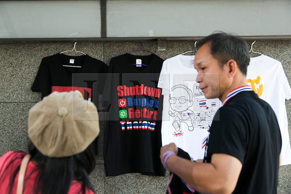 """© Licensed to London News Pictures. 05/01/2014. A vendor sells """"Shutdown Bangkok"""" T-shirts to a protestor during the third day of the 'Bangkok Shutdown' as anti-government protesters continue with their 'shutdown' of Bangkok.  Major intersections in the heart of the city have been blocked in their campaign to oust Prime Minister Yingluck Shinawatra and her government in Bangkok, Thailand. Photo credit : Asanka Brendon Ratnayake/LNP"""