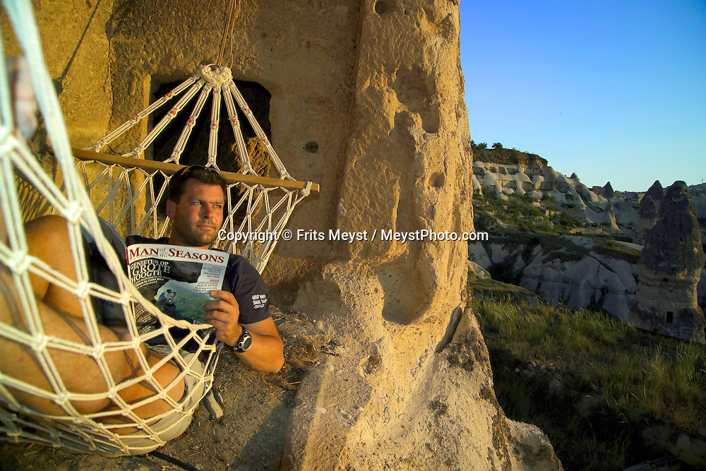 Goreme, Cappadocia, Turkey, July 2005. Dutch Frits takes a break in the Hammock. Photographer Frits Meyst and his wife Jillian Macdonald restored an old rock house in the village of Goreme. Since Roman Times people have been cutting graves and home out of the Soft tufo 'Fairy Chmney' rocks of Cappadocia. Photo by Frits Meyst/Adventure4ever.com