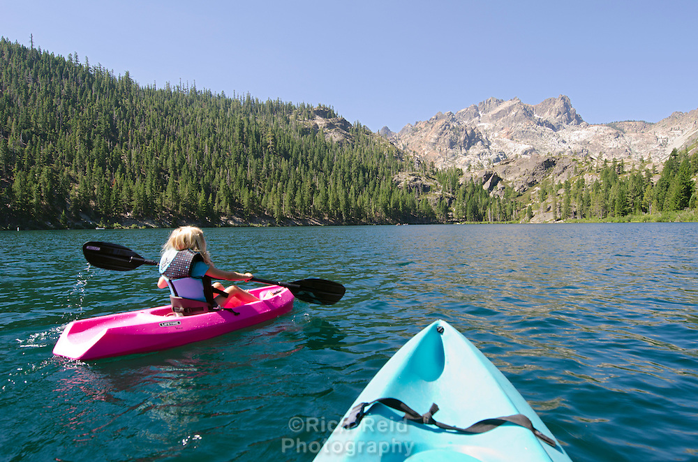 A young girl kayaking in Lower Sardine Lake below the Sierra Buttes in Tahoe National Forest, California.