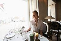 Portrait of smiling female customer sitting at restaurant table