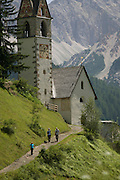 Walkers pass the church of Santa Berbura, founded and built by iron miners in 1490, in the Dolomites near La Val in Alta Badia, south Tyrol, Italy.