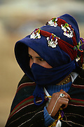 Young Ait Haddidou woman at the Imilchil Brides' Fair, the High Atlas, Morocco. The fair, or moussem, which is held by the local Berber tribe, is an annual event consisting of trading goods, praying at a marabout, the grave of a local saint, and searching for a suitable marriage partner. The way in which the woman wears her headdress tells that she is or has been married before.  Divorce is common in the area. Her clothing, e g the striped, woollen cloak, is typical of the Hait Haddidou women.