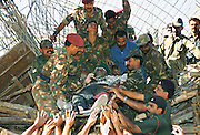 BANGALORE,1999.<br /> A body is removed by army personnel from the rubble of a building after it collapsed in the heavy rains in Bangalore.
