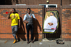 © Licensed to London News Pictures . 12/08/2017 . Manchester , UK . A portrait of Haile Selassie hanging from a gate as people gather along the route to watch the parade . The annual Caribbean Carnival J'Ouvert Parade through Moss Side in South Manchester . The 2017 theme is Bacchanal . There is concern in the community following the stabbing to death of Sait Mboob during a mass fight which saw several seriously hurt on Tuesday night (8th August 2017) . Photo credit : Joel Goodman/LNP