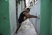 Namibia Flores in Santo Suarez Alley, the neighborhood where she lives in Havana.<br /> <br /> The Cuban boxing has a centennial long prestigious history written by exceptional champions, artists of the ring, whose legendary exploits , continue to live in the stories of fans. In 1962 Cuba had abolished professionalism in sports. Two years ago, driven by economic interests and attempt to stop the bleeding of athletes on the run from the island, sports authorities have announced participation in world boxing championship, the World Series of Boxing (WSB), which are not however a professional circuit because they remain part of the Olympic boxing. Thanks to a law passed a few years ago, with new economic conditions for the Cuban athletes, now, in addition to the contributions they receive from the state, the Cuban boxers will earn from their sport, 80% of the proceeds from participation in<br /> international sporting events. Another revolution in the land of revolutionary socialist utopia , now more and more on the road of the disintegration waiting for another revolution in the Cuban boxing that will allow women to have a women&rsquo;s boxing team. Revolution for which for years has fought Namibia Flores whose dream is to participate in the Olympics with the colors of his country. A fight against time for the forty Namibia Flores. A dream that will probably remain so for reached the age limit.<br /> Namibia has refused to fight for the US teams. Most likely it will not fight the next Olympics in Rio but it is determined to help future Cuban fighters to practice the sport which they love.