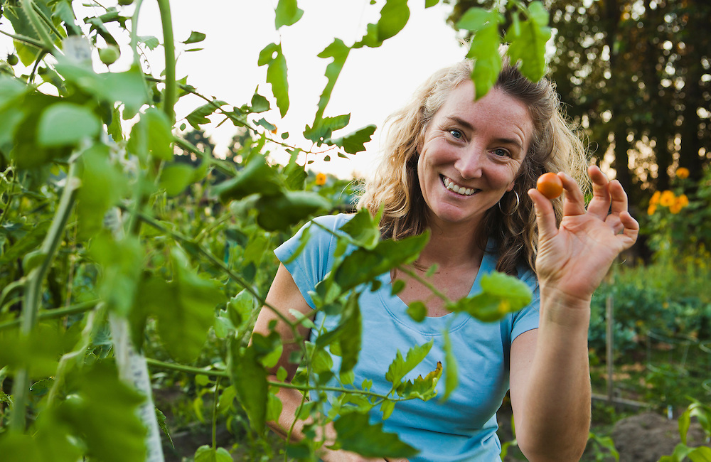 A middle aged woman smiling as she pick cherry tomatoes in her garden.