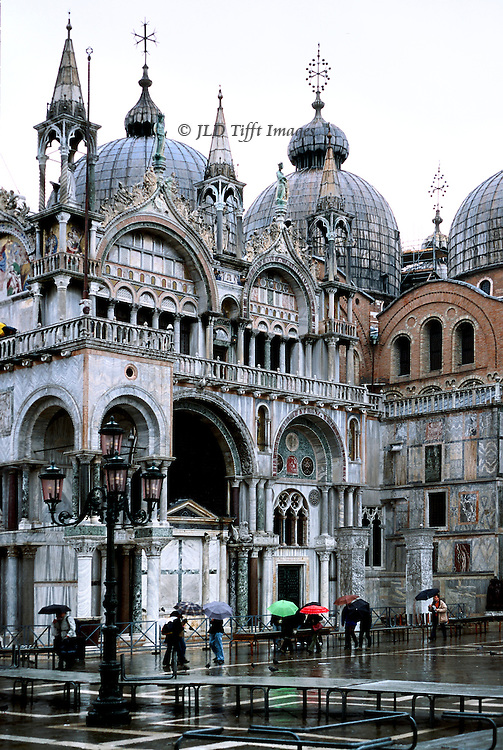 San Marco Basilica, western corner of the facade, in the rain.  Pedestrians holding umbrellas scurry past.  Raised walkways are in place in expectation of acqua alta.
