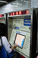 woman buys ticket from machine in a metro station in Shanghai China