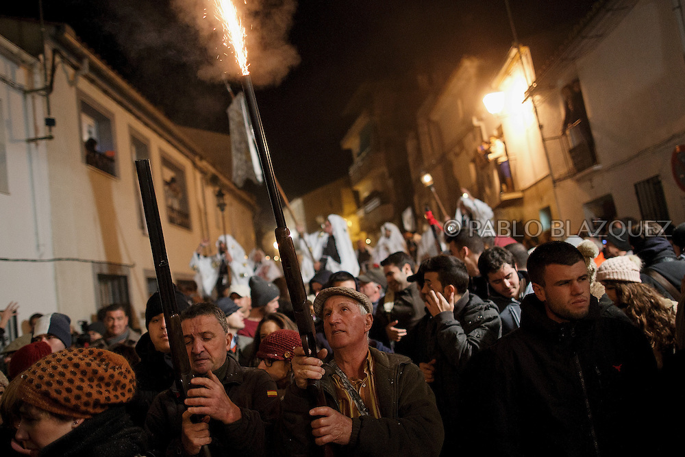 "Revelers shoot blanks with their shotguns during the ""La Encamisa"" Festival on December 7,  2014 in Torrejoncillo, Extremadura region, Spain. ""La Encamisa"" is an ancient festival in honor of Immaculate Conception. Hundreds of horsemen wearing a white sheet gather outside the church in the main square. The procession starts when a banner with the image of Immaculate Conception is delivered to the horse rider steward and people cheer and shoot blanks. There are bonfires along the way where people gather to chat, eat traditional sweets and drink local wine. The origin of this tradition is unknown but it is believed the festival comes from a military event in which people from Torrejoncillo were involved. The war in Flanders in 1585, the Battle of Pavia or a legend of the siege suffered by city of Coria. (© Pablo Blazquez)"