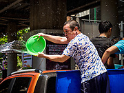13 APRIL 2018 - BANGKOK, THAILAND:  A Thai man in the bed of a pickup truck throws a bucket of water on people on Silom Road during the first day of Songkran in Bangkok. Songkran is the traditional Thai New Year celebration best known for water fights.    PHOTO BY JACK KURTZ