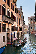 "Gondolas are traditional, flat-bottomed rowing boats which ferry people through Venetian canals. From a peak of 10,000 gondolas 200 years ago, just 500 gondolas now serve Venice. The banana-shaped modern gondola was developed in the 1800s. The left side of the gondola is made longer than the right side to resist leftwards drift at the forward stroke. The gondolier stands on the stern facing the bow and rows just on the right side, with a forward stroke and compensating backward stroke. The oar or rèmo is held in an oar lock, or fórcola, shaped for several rowing positions. The decorative fèrro (meaning iron) ornament on the front can be made of brass, stainless steel, or aluminum, as counterweight for the gondolier standing near the stern. The six horizontal lines and curved top of the ferro represent Venice's six sestieri (districts) and the Doge's cap. Painting gondolas black originated as a sumptuary law banning ostentatious competition between nobles. Until the early 1900s, many gondolas had a small cabin (felze) with windows which could be closed with louvered shutters--the original ""venetian blinds."" The romantic ""City of Canals"" stretches across 117 small islands in the marshy Venetian Lagoon along the Adriatic Sea in northeast Italy, Europe. Venice and the Venetian Lagoons are honored on UNESCO's World Heritage List."