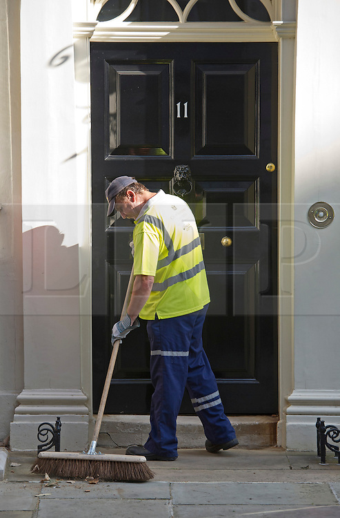© London News Pictures. 04/09/2012. London, UK.  A council road cleaner cleaning dirt and rubbish from in front of Number 11 Downing Street on the day of cabinet reshuffle September 04, 2012. Photo credit: Ben Cawthra/LNP