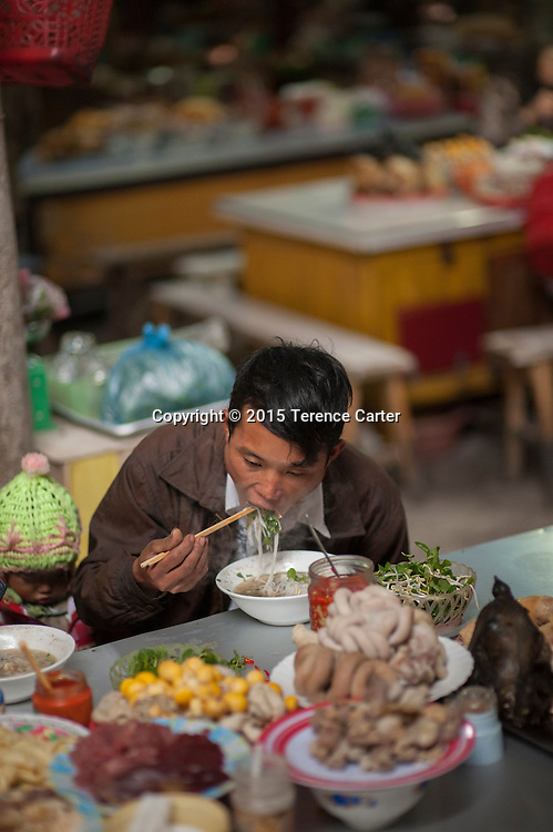 A man slurps a noodle soup for lunch in the markets of Sapa, Vietnam.