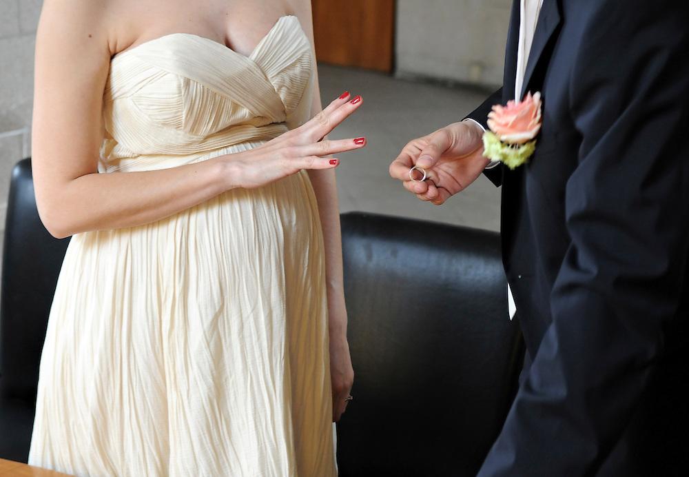 Im Standesamt hält ein Bräutigam den Ehering vor dem Ringfinger seiner zukünftigen Ehefrau.   Junges Paar anlässlich der Eheschließung |    marriage of a young couple     |