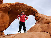 Mati Reed (age 11) climbs Arch Rock sandstone formation at Valley of Fire State Park, Moapa, NV.  Less than an hour, northwest of Las Vegas this secluded valley contains dramatic red sandstone formations. ..PHOTO COPYRIGHT 2006 LANCE CHEUNG<br />