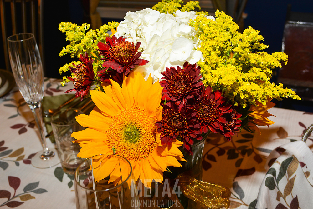 A beautiful floral arrangement forms the perfect backdrop for a festive meal.