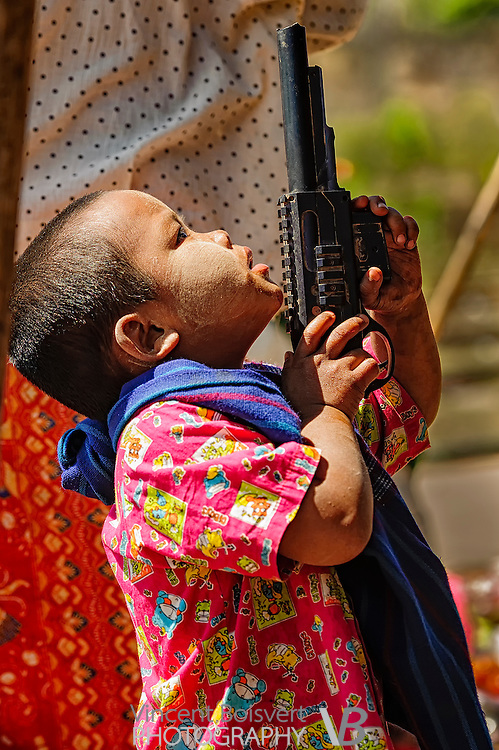a young burmese boy playing with a toy gun and looking up