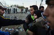 An Iranian protester pushes a Syrian couple, preventing them from getting near the Greek border crossing to Macedonia near the town of Idomeni on December 2, 2015. A group of predominantly Iranian and Moroccan asylum seekers barricaded the border crossing about an hour earlier and began physically blocking Syrians, Iraqis and Afghanis from approaching the border in protest of Macedonia's border restrictions. On November 17, 2015 Macedonia, Serbia, Slovenia and Croatia enacted border restrictions which blocked all asylum seekers, except those with documents proving they were from Syria, Iraq and Afhanistan, from entering any of those countries. According to UNHCR, over 60,000 asylum seekers are currently stranded in Greece due to these restrictions.