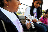 """Flora Cristobal, left, holds a cross with the name of her son Rodolfo, who was a victim of violence. Rodolfo's sister Cristina wears a shirt with her brother's photograph on it - on the right is her sister Barbara. On Sunday in Closter Park, the group """"A Time for Grieving and Healing"""" led by Debbie Aguilar unveiled a memorial to the numerous victims of violence in Monterey County."""