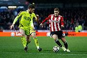 Brentford Midfielder Lewis Macleod (4) looks to take on Notts County defender Matt Tootle (2) during the The FA Cup 3rd round match between Brentford and Notts County at Griffin Park, London, England on 6 January 2018. Photo by Andy Walter.