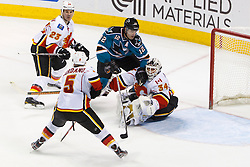 Feb 8, 2012; San Jose, CA, USA; San Jose Sharks left wing Patrick Marleau (12) collides with Calgary Flames goalie Miikka Kiprusoff (34) in front of the goal during the third period at HP Pavilion. Calgary defeated San Jose 4-3. Mandatory Credit: Jason O. Watson-US PRESSWIRE