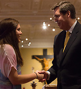 Venezia Hyland shakes the hand of President Thayne McCulloh at the social justice missioning ceremony. Photo by Libby Kamrowski
