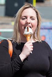 © Licensed to London News Pictures. 30/04/2016. Brighton, UK. A woman enjoys an ice cream on Brighton Promenade as the seaside resort basks in sunshine this May bank holiday weekend. Photo credit: Hugo Michiels/LNP