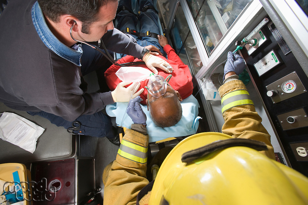 Firefighter and paramedic helping man in ambulance