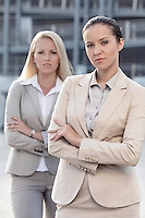 Portrait of confident young businesswomen standing arms crossed outdoors
