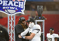 UCF Knights linebacker Shaquem Griffin (L) and quarterback McKenzie Milton (10) celebrate after the second half of the Chick-fil-A Peach Bowl NCAA college football game at the Mercedes-Benz Stadium in Atlanta, January 1, 2018. UCF won 34-27 to go undefeated for the season. (David Tulis via Abell Images for Chick-fil-A Peach Bowl)