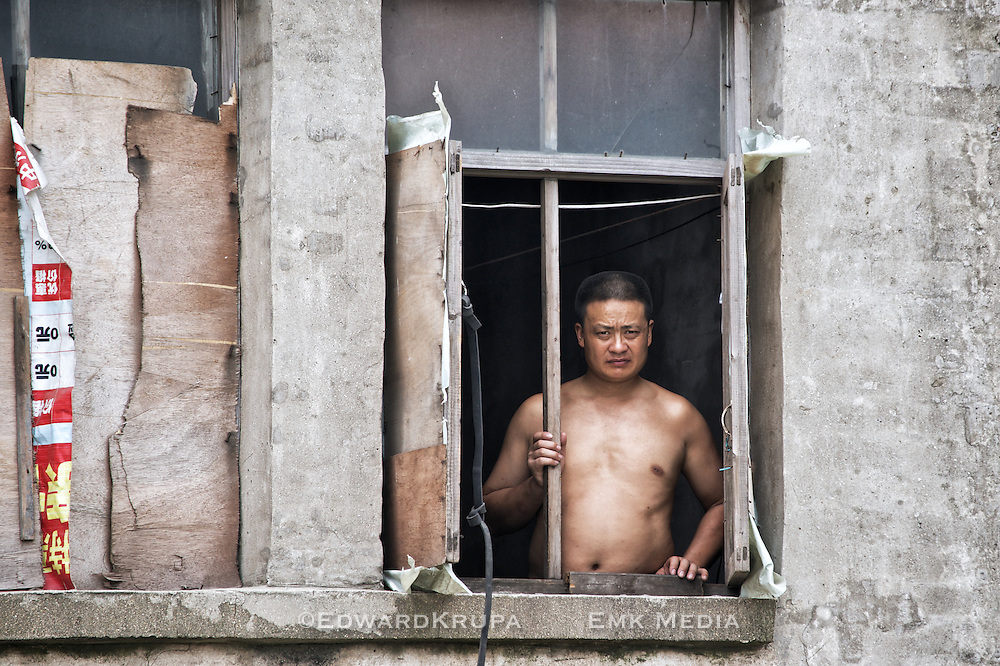 A man looking out a window in a village in rural China.