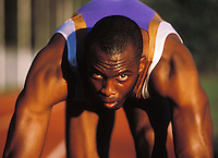 Late 20's African American Man set to start a sprint looking intensly down the track.<br />