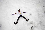 "A girl lays on snow during the annual ""Christmas in July"" event at the Union Rescue Mission in the Skid Row area of Los Angeles, California on Wednesday, July 10, 2013. (Photo by Ringo Chiu/PHOTOFORMULA.com)"